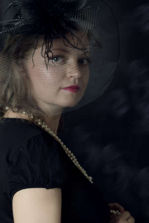 Elegant retro woman in veil over dark background photo