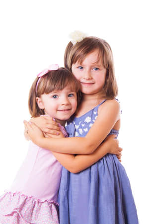 Two happy sisters hugging isolated on white photo