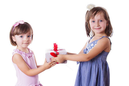 Happy little sisters holding present isolated on white background photo
