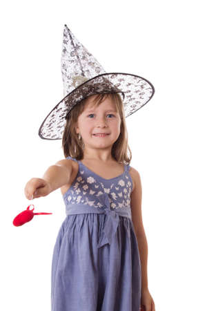 Adorable girl making magic with wand isolated on white Stock Photo