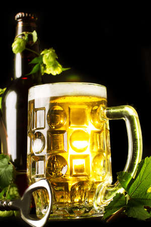 Mug of golden beer, bottle and openner with hop leaves over black photo