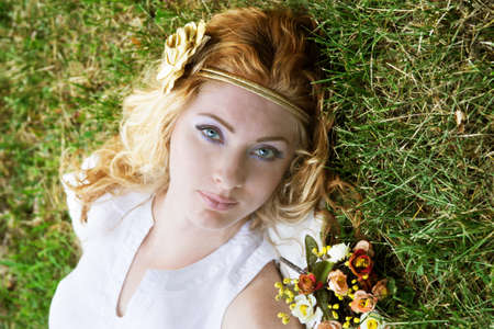 Romantic red-headed woman lying on green grass photo