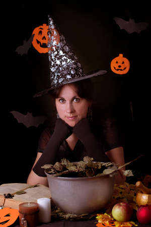 Nice witch practicing sorcery at Halloween night photo