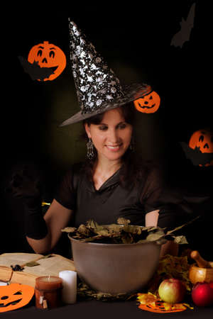 sorcery: Smiling witch practicing sorcery at Halloween night Stock Photo