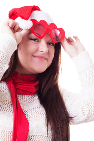 Smiling woman in Santa hat lifting heart-shaped glasses up isolated on white Stock Photo - 22471109