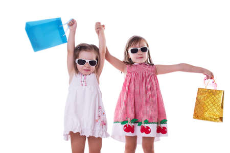 Two happy little girls in sun-glasses and shopping bags isolated on white photo