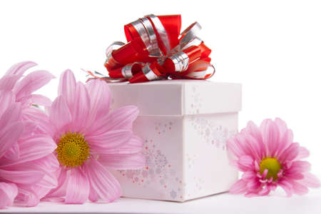 Gift-box with red bow with pink daisies over white photo