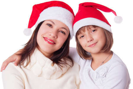 Smiling mother and daughter in Santa hats isolated on white Stock Photo - 23050234