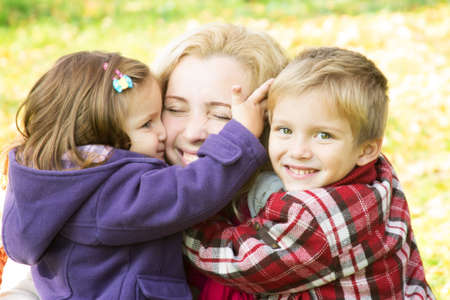 Two children hugging mother, focus on boy photo