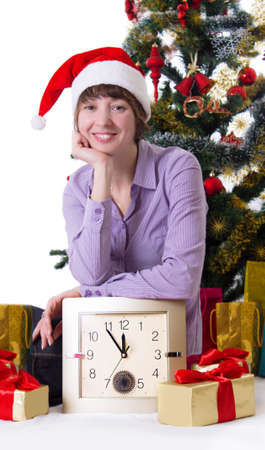 Smiling woman with clock under Christmas tree on white Stock Photo - 23575498