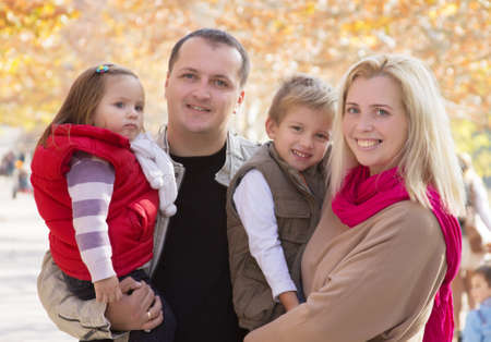 Happy family with two children in autumn park photo