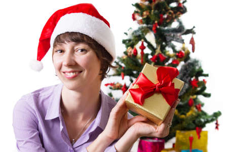 Smiling woman in Santa hat with present under Cristmas tree over white Stock Photo - 23575507