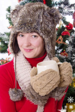 Smiling woman in fluffy hat and mitten under Christmas tree with cup Stock Photo - 23575509
