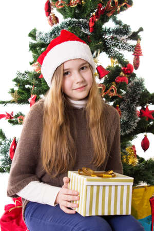 Cute teenage girl in Santa hat with present under Christmas tree Stock Photo - 23577309