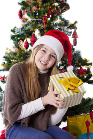 Cute teenage girl in Santa hat with present under Christmas tree Stock Photo - 23577310