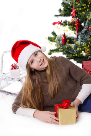Cute teen girl in Santa hat with gifts under Christmas tree Stock Photo - 23577311