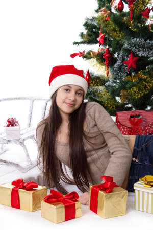 Smiling teen girl in Santa hat with gifts under Christmas tree Stock Photo - 23577313