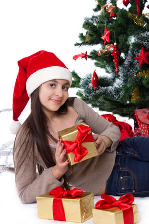 Smiling teen girl in Santa hat with gifts under Christmas tree Stock Photo - 23577316