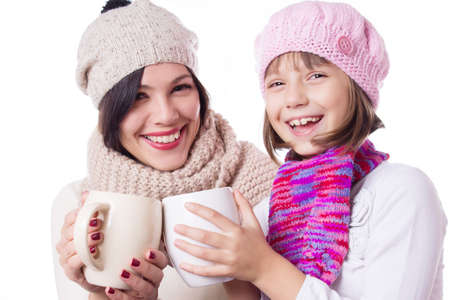 Happy mother and daughter in knitted hats with hot beverages over white photo