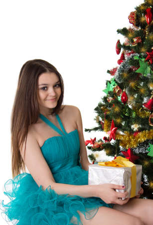 Pretty girl in fancy dress under Christmas tree with gift over white photo
