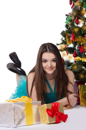 Beautiful teenage girl in fancy dress under Christmas tree over white photo