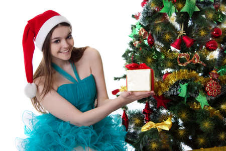 Smiling teenage girl in Santa hat offering present under Christmas tree over white photo