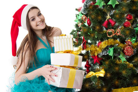 Smiling Santa helper girl with pile of presents under Christmas tree photo