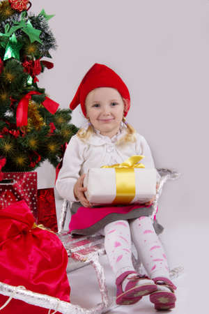 Little girl in Santa hat with present on sledge under Christmas tree photo