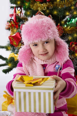 chritmas: Pretty girl in pink fur hat holding present under Chritmas tree Stock Photo