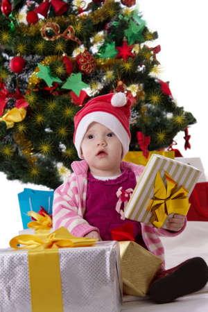 Cute little girl in Santa hat sitting under Christmas tree over white photo