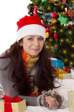 Lovely woman in Santa hat and fur mittens lying under Christmas tree Stock Photo - 24210103