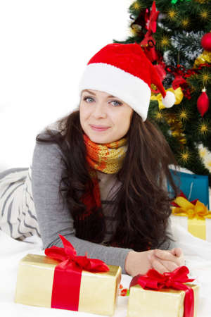 Smiling woman in Santa hat lying under Christmas tree over white Stock Photo - 24210104