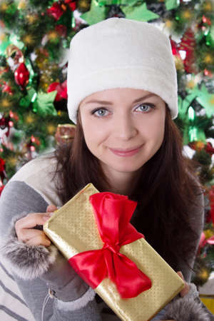 Smiling woman in fur hat and mitten holding Christmas present Stock Photo - 24210105