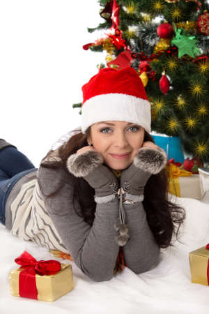 Cute woman in Santa hat and fur mittens lying under Christmas tree Stock Photo - 24210107