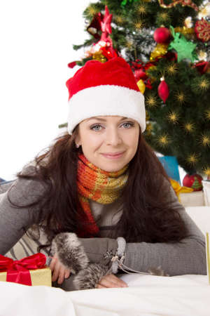 Smiling woman in Santa hat and fur mittens lying under Christmas tree Stock Photo - 24210108