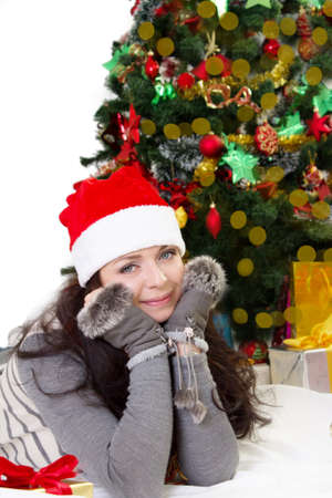 Smiling woman in Santa hat and fur mittens lying under Christmas tree Stock Photo - 24210109