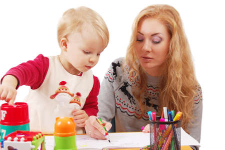 Little daughter learning to draw with her mother over white photo