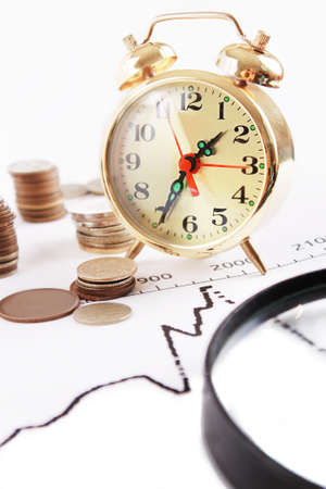 Magnifying glass, alarm clock with pile of coins on growth graphics  photo