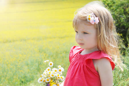 Sweet baby girl among rapeseed field with camomile bouquet photo