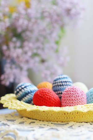 Basket of handmade knitted Easter eggs and lilac flower photo