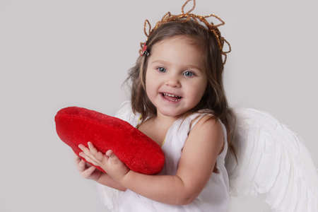 Happy cupid girl holds plush heart isolated on white photo