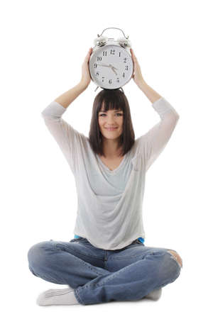 Smiling girl with clock on head in lotus pose over white photo