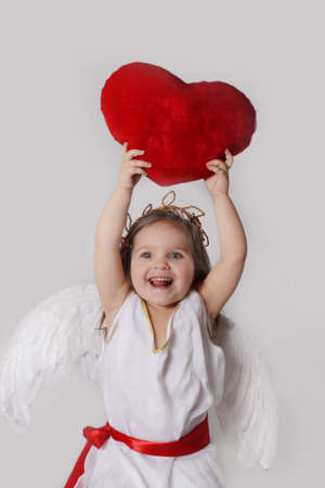 Joyful cupid girl holds plush heart over head isolated onmwhite photo