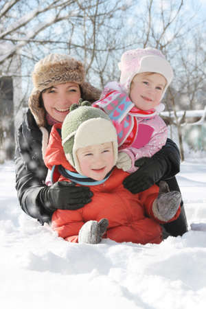 Happy mother with two children lying in snow photo