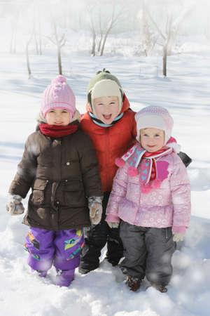 winterwear: Three happy children having fun in winter