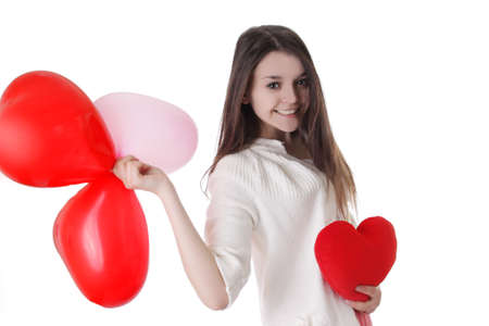 Smiling young girl with balloons and plush heart over white photo