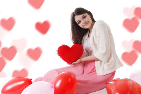 Young girl with red balloons on heart-shaped bokeh background photo