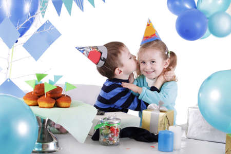 Two children celebrating birthday at party table over white photo