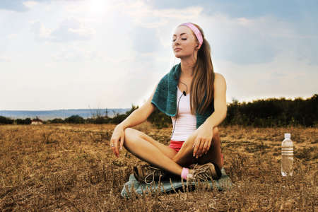meditates: Sporty woman with headphones meditates at sunset time