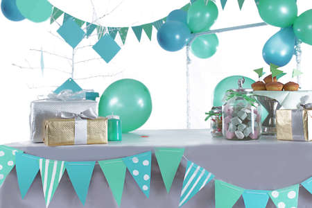 table decorations: Blue and green colored birthday party table with sweets and decorations Stock Photo